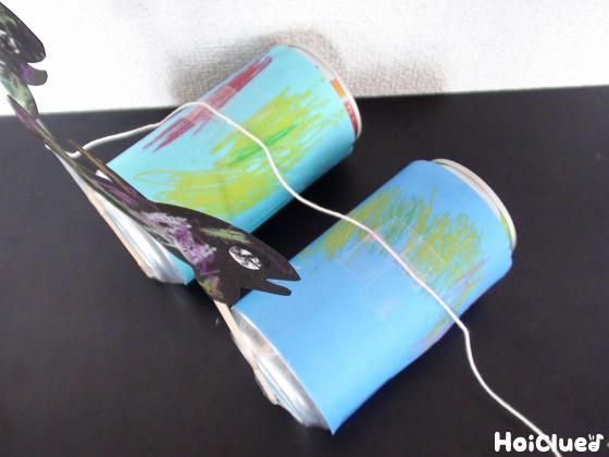 並べた空き缶の上にタコ糸を取り付け、たけひごにクジラを貼り付けた写真