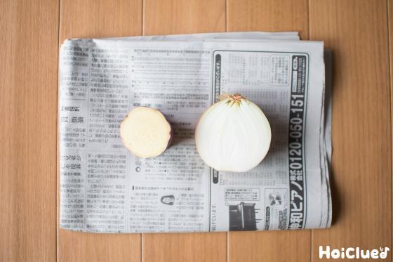 新聞紙の上に置いた輪切りにした玉ねぎとサツマイモの写真