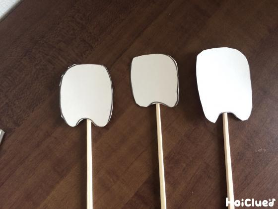 歯型に切った牛乳パックに割り箸を取り付けた写真