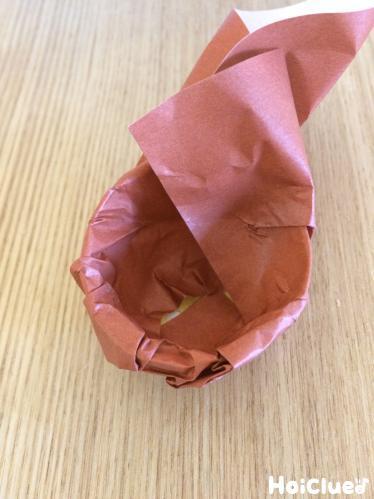 容器を折り紙で包み込む様子