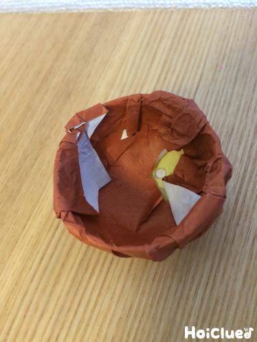 折り紙の余りを容器の内側に折り込む様子