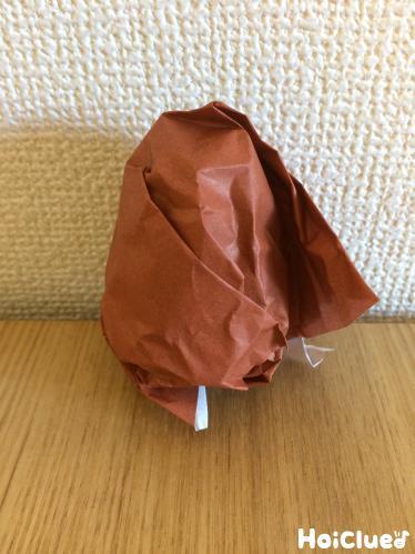 新聞紙を折り紙で包み込む様子