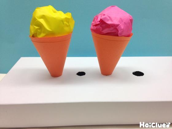 穴を開けた空き箱にアイスクリームを差し込んだ写真