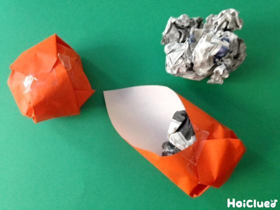 丸めた新聞紙をオレンジの折り紙で包む様子