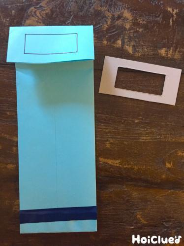 縦にした画用紙の下を折りビニールテープでとめ、上の持ち手のくり抜く線を描いた写真