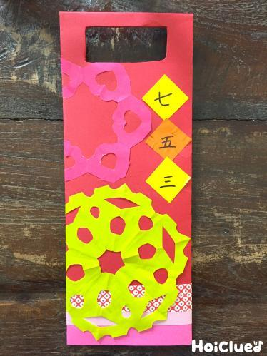 折り紙飾りを貼り完成した千歳飴袋の写真