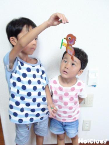 輪ゴムを伸ばすように両端のストローを手に持つ子どもの様子