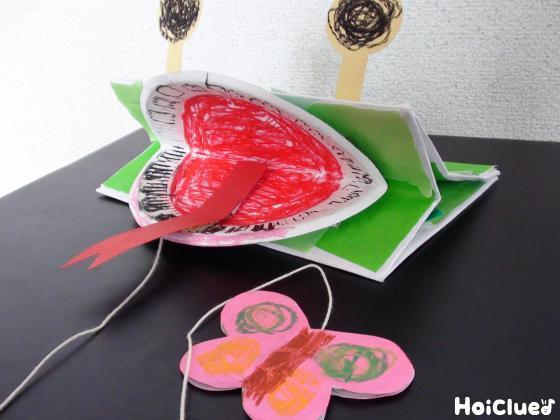 紙袋の底に紙皿を挟み固定し、舌とタコ糸を付け完成したカエルの写真