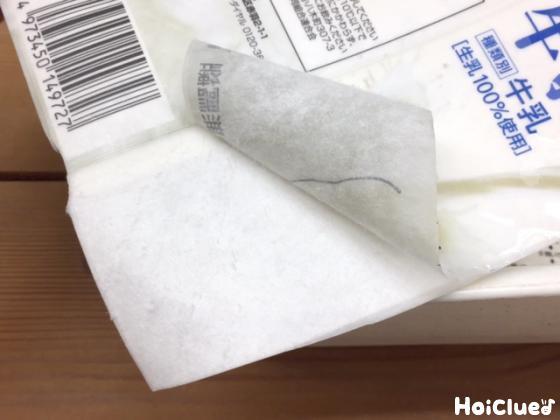 牛乳パックの外側のシールを剥がしている写真