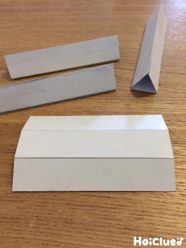 厚紙で三角の筒を作る様子