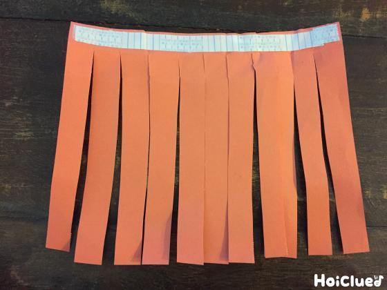 オレンジの画用紙に切り込みを入れ両面テープを貼った写真