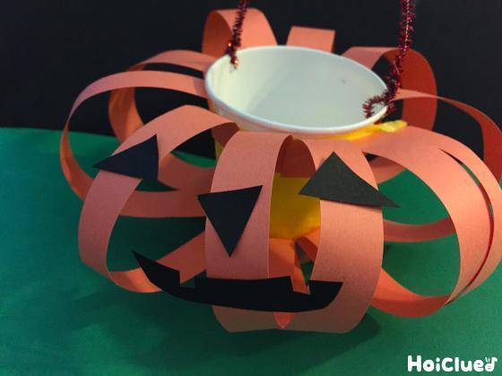 黒い画用紙で顔を貼り完成たかぼちゃバッグの写真