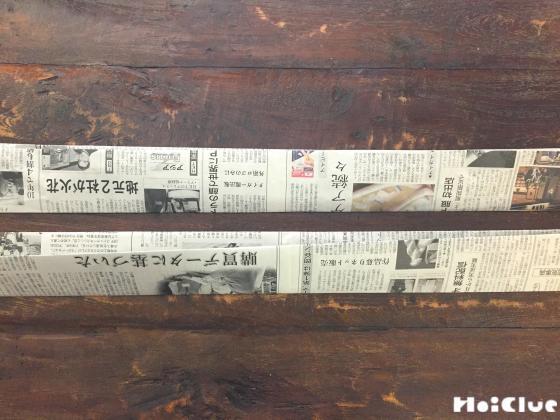 細長く折った新聞紙の写真
