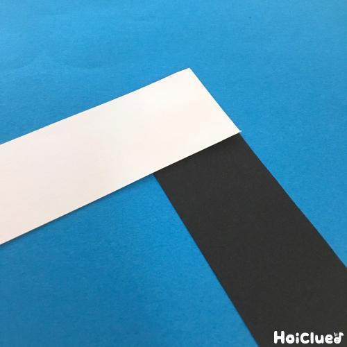 白黒の2つの画用紙を細く切り取った写真