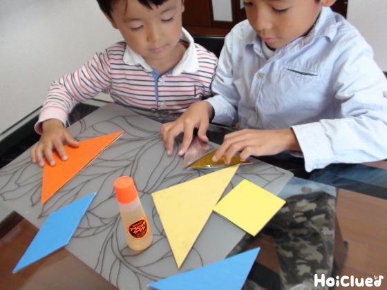 ダンボールに色画用紙を貼る子どもたちの様子