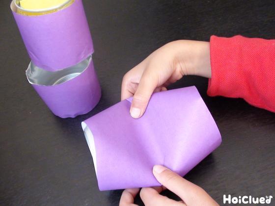 空き缶に色画用紙を巻き半分に切る様子
