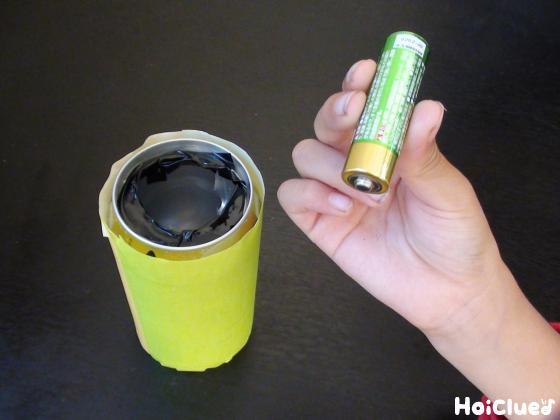 折り紙を巻いた空き缶と乾電池の写真 title=