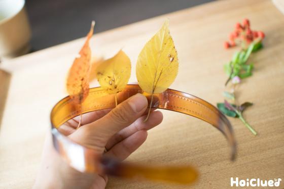 セロハンテープでカチューチャに落ち葉を貼り付けている写真