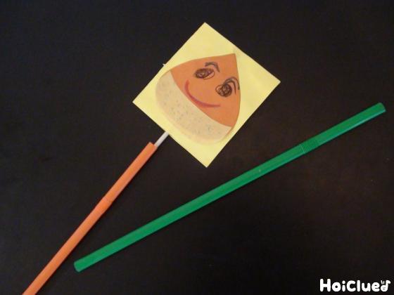 竹串を挟み込むように画用紙を貼り合わせた写真