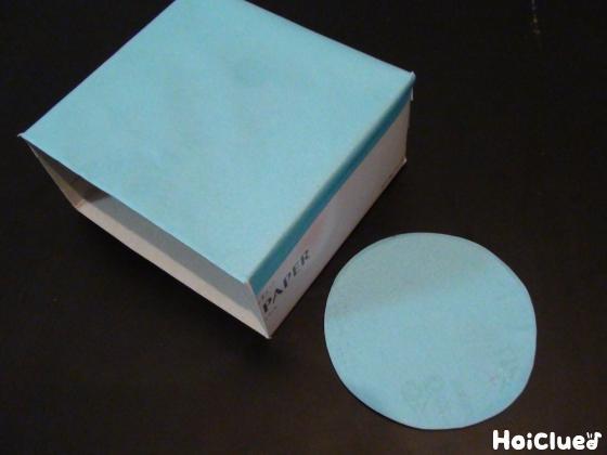 ティッシュ箱を半分に切って折り紙をはり、丸を作った写真
