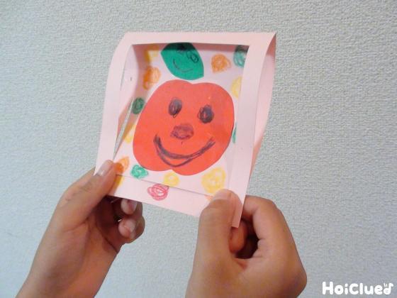 両手で完成品の画用紙を持っている写真