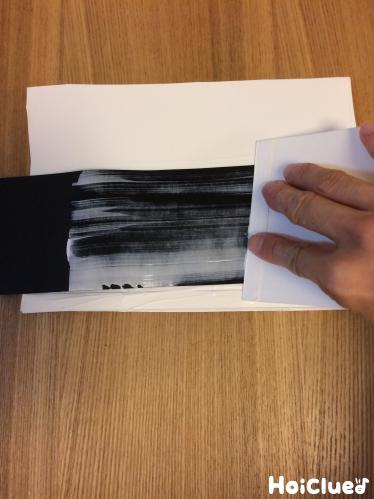 牛乳パックに黒い画用紙を貼り付けている写真