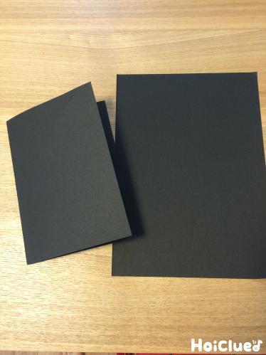 黒い画用紙を折っている写真