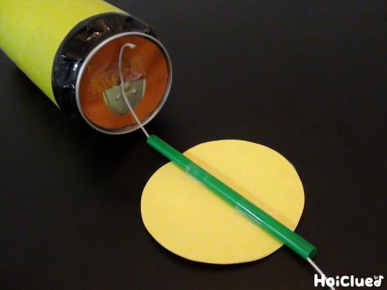 丸い画用紙にストローを貼りタコ糸を通し、空き缶に固定した様子