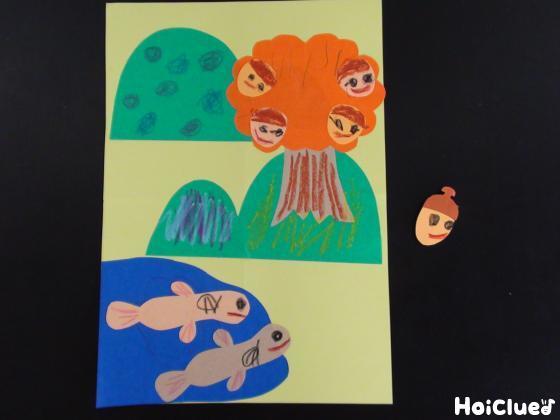 ドジョウやどんぐりのパーツを画用紙に貼った写真