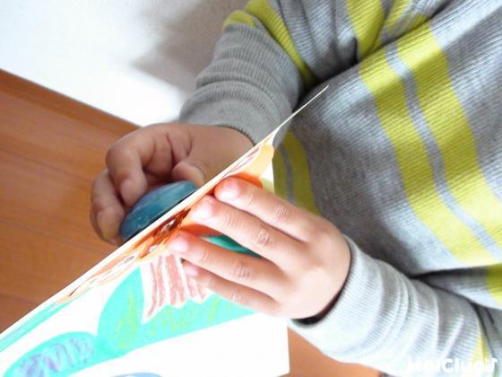 画用紙を挟み磁石とどんぐりをくっつける子どもの様子