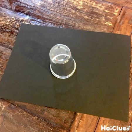 黒い画用紙の上にクリアカップだけがある写真