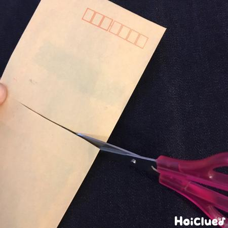 封筒の真ん中に切り込みを入れている写真