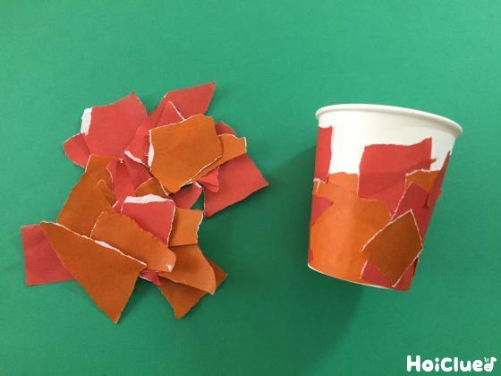 破いた折り紙を紙コップに貼る様子