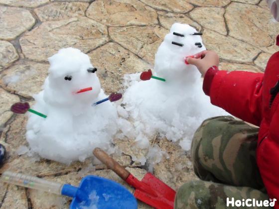 雪だるまに目鼻手の部品を埋め込んでいる写真