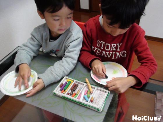 紙皿に模様を描く子どもたちの様子