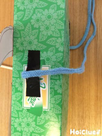 箱の側面に紐を取り付ける様子