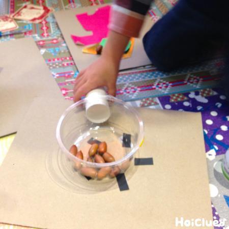コンロに鍋を乗せどんぐりを調理する子どもの様子