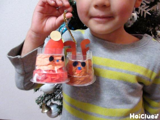 完成したクリスマス飾りを手に持つ子どもの写真