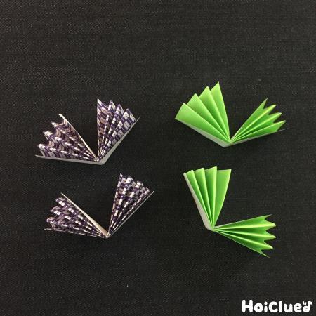 折り紙を蛇腹折りして蝶々みたいにしている写真