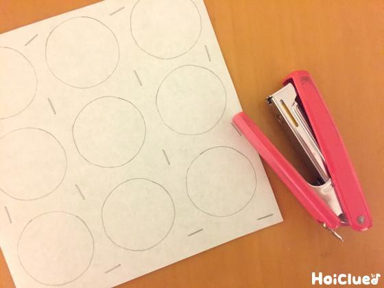描いた丸の間をホチキス留めした写真