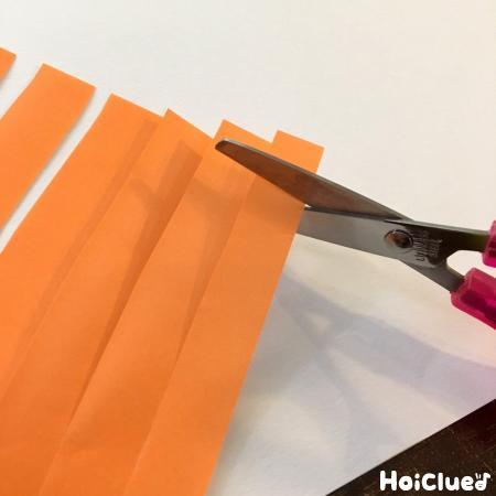 切り込みを入れた折り紙を切る様子