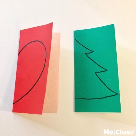 半分に折った折り紙にハートと木を半分描いた写真