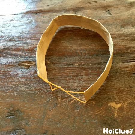 細長く切った紙袋の両端を輪ゴムで止めている写真