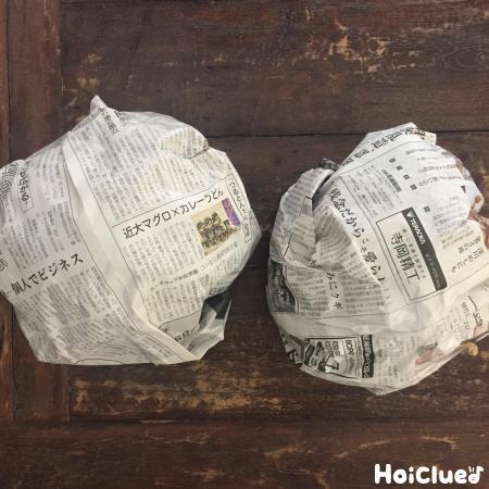 新聞紙を二つ丸めた写真
