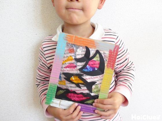完成したステンドグラスを手に持つ子どもの写真