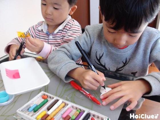 絵を描きセロファンを切る子どもたちの様子