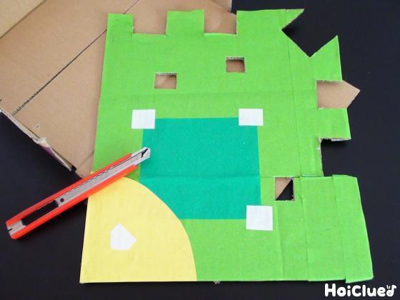四角いダンボールに折り紙を貼り何箇所か四角くくり抜いた写真