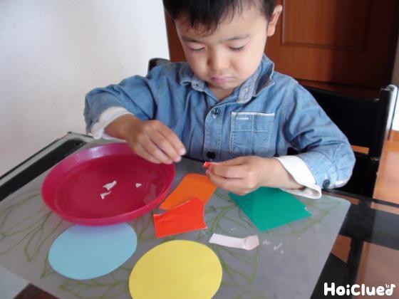 ちぎった色画用紙を貼る子どもの様子