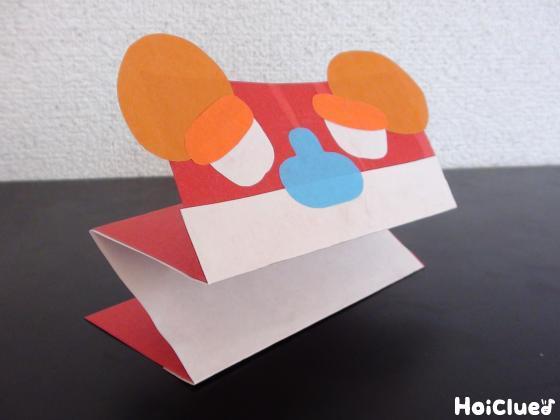 貼り合わせた画用紙をじゃばら折りにし顔のパーツを貼った写真
