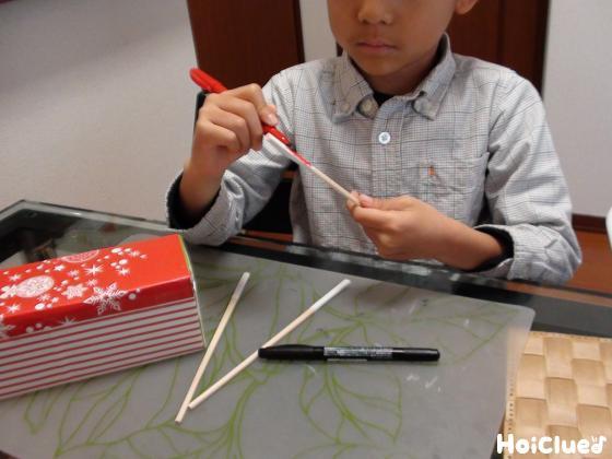 割り箸に文字を書く子どもの様子